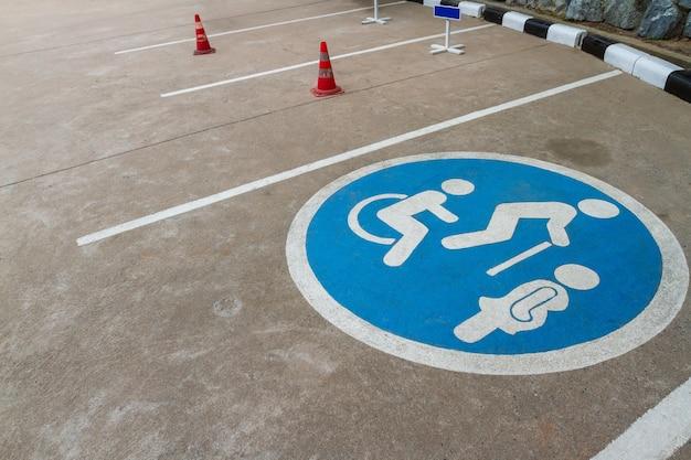 Obraz niebieskiego punktu wolnego miejsca parkingu samochodów z wózkiem inwalidzkim lub osobą niepełnosprawną