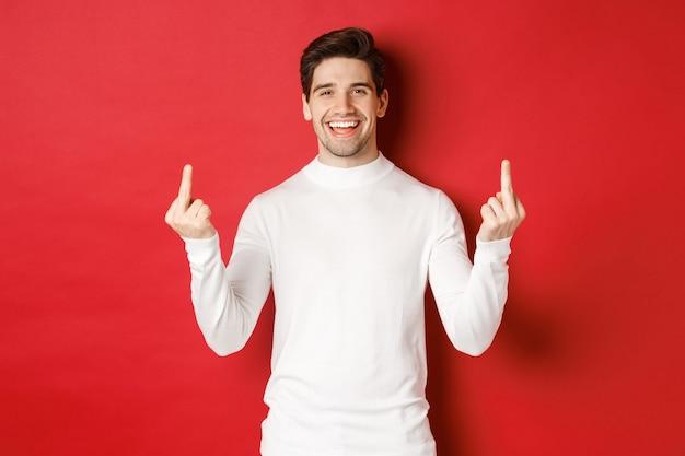Obraz niegrzecznego i niezmąconego mężczyzny śmiejącego się, pokazującego środkowe palce mówiące, żeby się spierdalać, stojąc na...