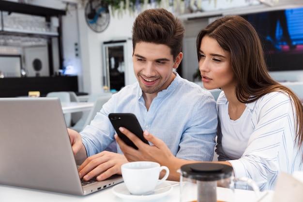 Obraz niesamowitej młodej pary miłości siedzi w kawiarni przy użyciu komputera przenośnego i telefonu komórkowego.