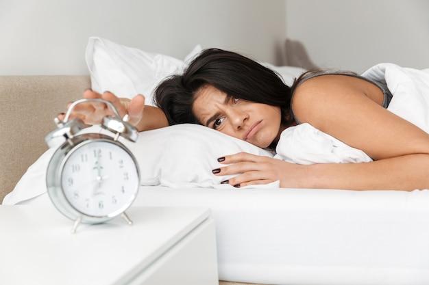 Obraz niezadowolonej kobiety 20s leżącej w łóżku na poduszce i wyłączającej dzwoniący budzik na nocnej szafce