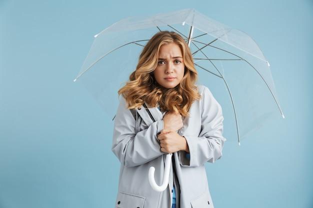 Obraz niezadowolonej kobiety w wieku 20 lat w płaszczu przeciwdeszczowym, stojącej pod przezroczystym parasolem
