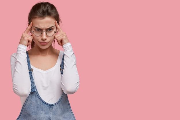 Obraz niezadowolonej młodej damy trzyma oba palce wskazujące na skroniach, cierpi na migrenę, nosi okrągłe okulary