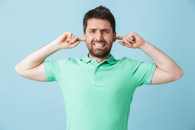 Obraz niezadowolony młody przystojny brodaty mężczyzna pozowanie na białym tle nad niebieskimi ścianami obejmującymi uszy z powodu głośnego.
