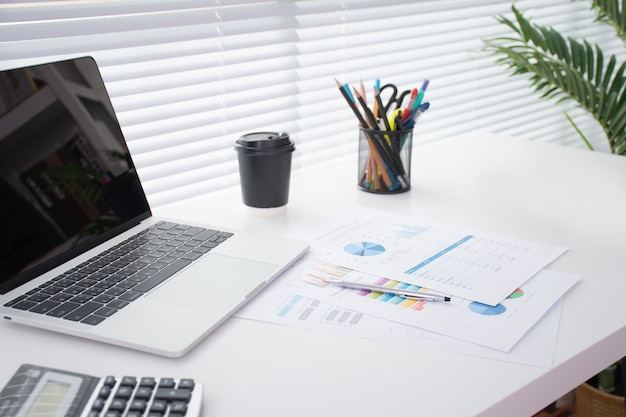 Obraz nowoczesnego biurka z laptopem, długopisem, kalkulatorem i dużym stosem dokumentów na białym biurku w pobliżu dużego okna.