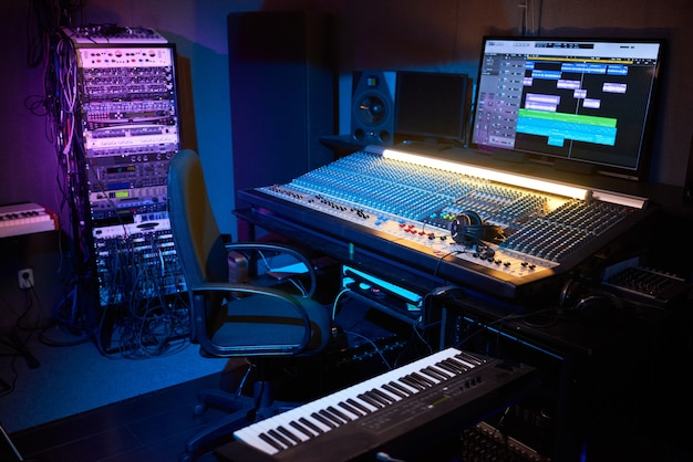 Obraz nowoczesnego ciemnego studia nagrań z komputerem i instrumentami muzycznymi