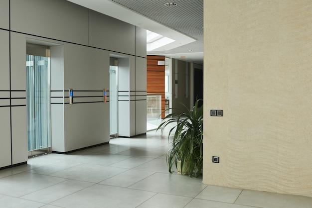 Obraz nowoczesnego korytarza z windą ze szklanymi drzwiami w biurowcu