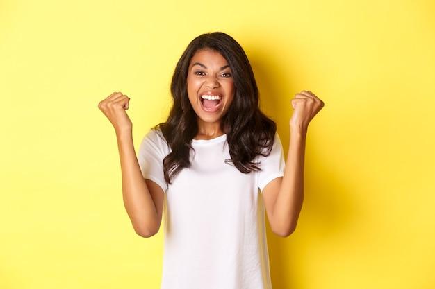 Obraz odnoszącej sukcesy afroamerykańskiej dziewczyny, która czuje się szczęśliwa, robi znak pompki pięścią i mówi tak, triumfuje i krzyczy z radości, stojąc na żółtym tle.