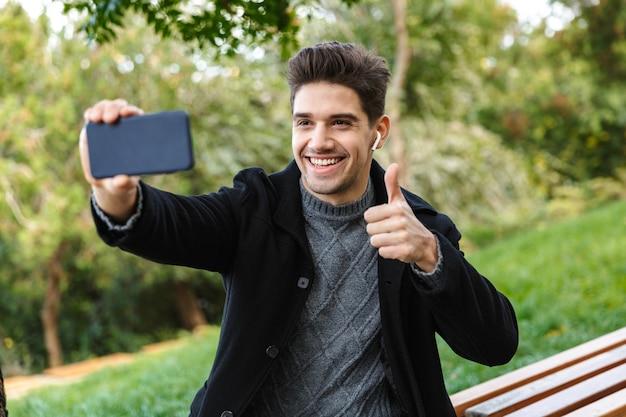 Obraz optymistycznego młodego człowieka w odzieży casual spaceru na świeżym powietrzu w zielonym parku przy użyciu telefonu komórkowego weź selfie z kciuki do góry gestem.