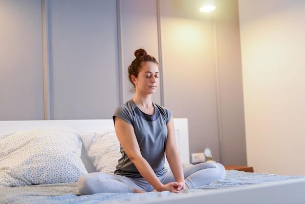 Obraz pasuje pięknej kobiety w średnim wieku, siedząc na łóżku w pozycji lotosu.