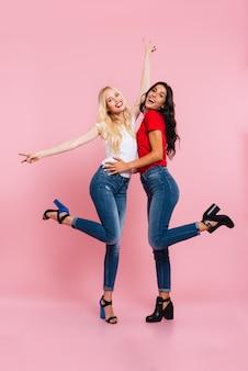 Obraz pełnej długości dwóch rozochoconych kobiet cieszy się i patrzy w kamerę na różowo