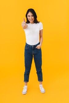 Obraz pełnej długości młodej brunetki azjatyckiej kobiety uśmiecha się i gestykuluje kciukiem odizolowanym na żółto