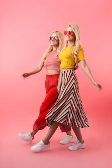 Obraz pełnej długości przedstawiający szczęśliwe blond bliźniaczki w okularach przeciwsłonecznych spacerujących razem po różowej ścianie