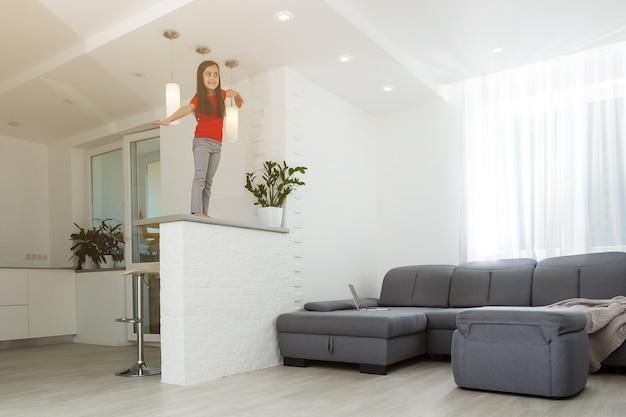 Obraz pełnometrażowy mała córka zabawy wygłupiać się w domu sportowe aktywne dziecko dziewczynka. zabawne zajęcia rekreacyjne, koncepcja sportowego zdrowego stylu życia