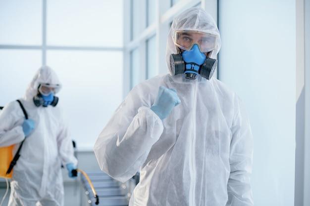Obraz pewnego siebie mężczyzny odkażającego stojącego w holu biura. pojęcie ochrony zdrowia.