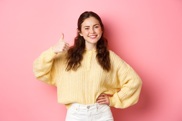 Obraz pewnej siebie uśmiechniętej dziewczyny pokazuje swoje wsparcie, podnosi kciuki z aprobatą, lubi i zgadza się z tobą, pochwala dobry wybór, stoi na różowej ścianie.