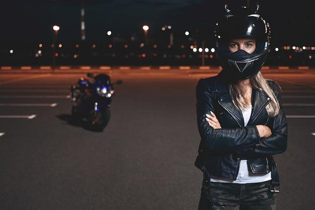Obraz pewnej siebie, zdeterminowanej, młodej jeźdźca w kasku ochronnym stojącej na parkingu, trzymającej ręce skrzyżowane i patrząc, jadącej na motocyklu po mieście nocą
