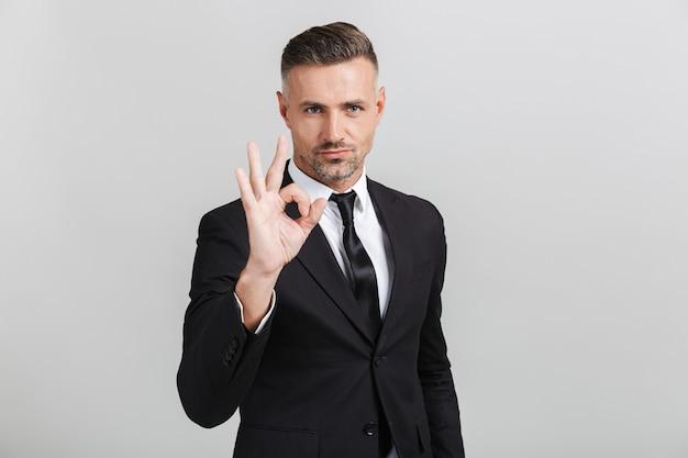 Obraz pewny siebie dorosłego biznesmena w formalnym garniturze, wskazującego ok śpiewać na białym tle
