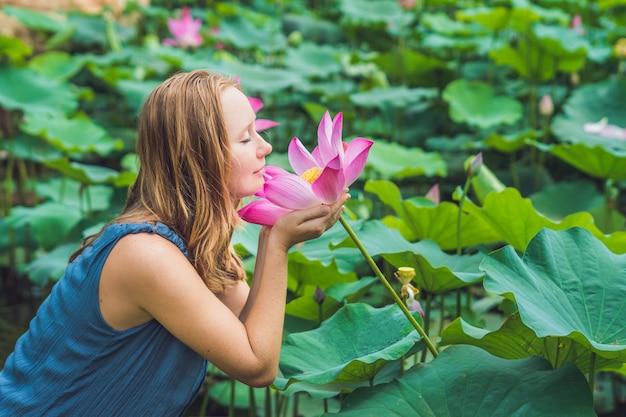 Obraz piękna kobieta rudowłosa z kwiatem lotosu w dłoni.