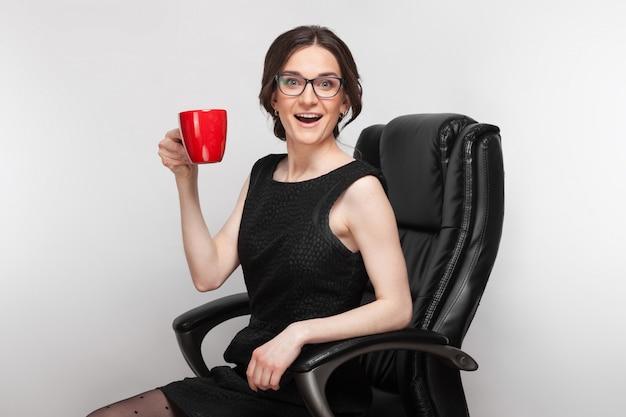 Obraz piękna kobieta w czarnej sukni siedzi w fotelu z kawą w ręce