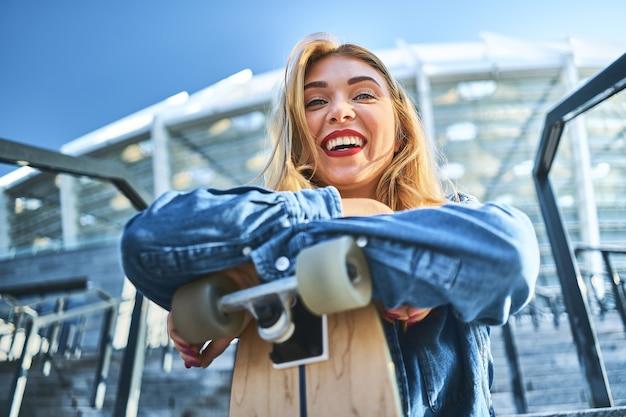 Obraz piękna stylowa uśmiechnięta kobieta siedzi na schodach ulicy w letni dzień i trzyma deskorolkę.