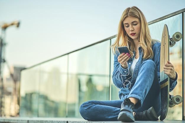 Obraz piękna stylowa uśmiechnięta kobieta siedzi na schodach ulicy w letni dzień z deskorolką