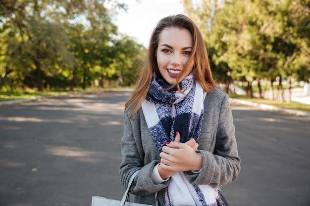 Obraz piękna szczęśliwa młoda kobieta nosi szalik, uśmiechając się na tle przyrody i trzymając torbę.