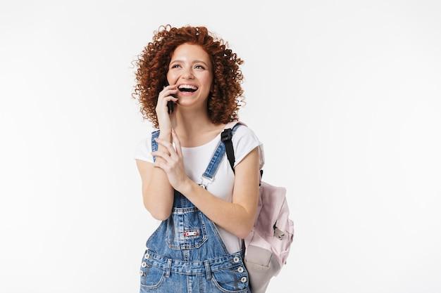 Obraz piękne kręcone szczęśliwy rude dziewczyny pozowanie na białym tle nad białą ścianą rozmawia przez telefon komórkowy.