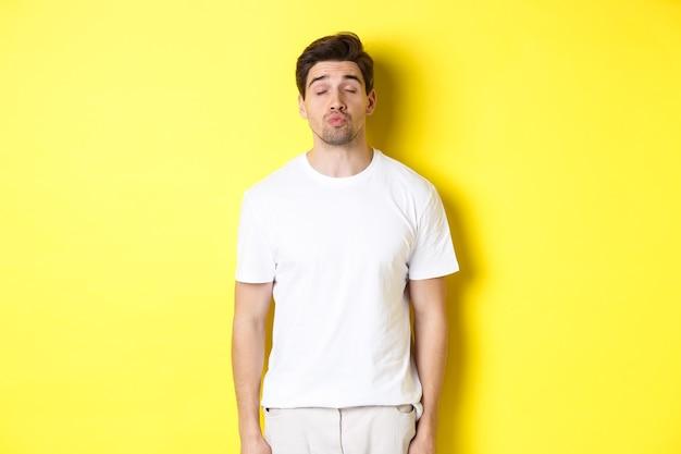 Obraz pięknego mężczyzny zamyka oczy i zmarszczone usta, czekając na pocałunek, stojąc w białych ubraniach na żółtym tle. skopiuj miejsce