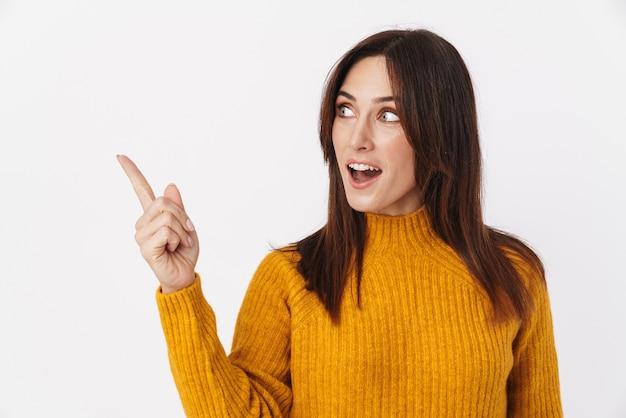 Obraz pięknej brunetki dorosłej kobiety noszącej sweter uśmiechający się i wskazujący palcem na bok na copyspace na białym tle