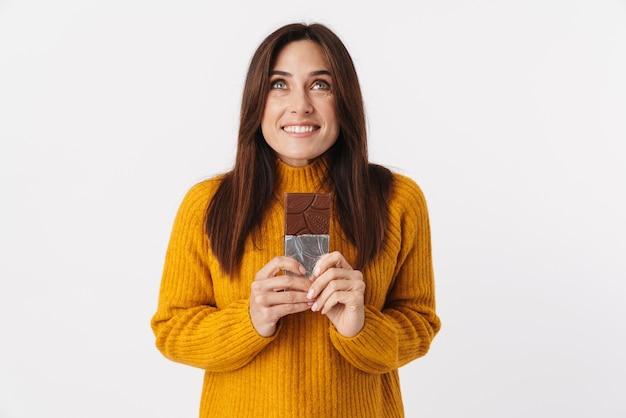 Obraz pięknej brunetki dorosłej kobiety uśmiechającej się i trzymającej tabliczkę czekolady na białym tle