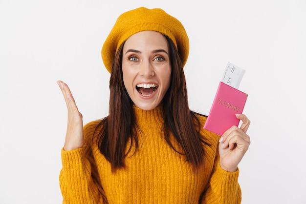 Obraz pięknej brunetki dorosłej kobiety w berecie, uśmiechniętej i trzymającej bilety podróżne na białym tle