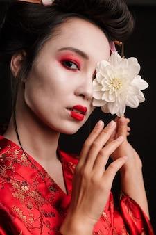 Obraz pięknej gejszy kobiety w tradycyjnym japońskim kimonie trzyma kwiat