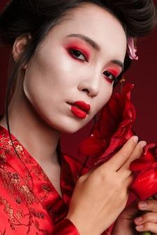 Obraz pięknej gejszy kobiety w tradycyjnym japońskim kimonie trzymającej kwiaty