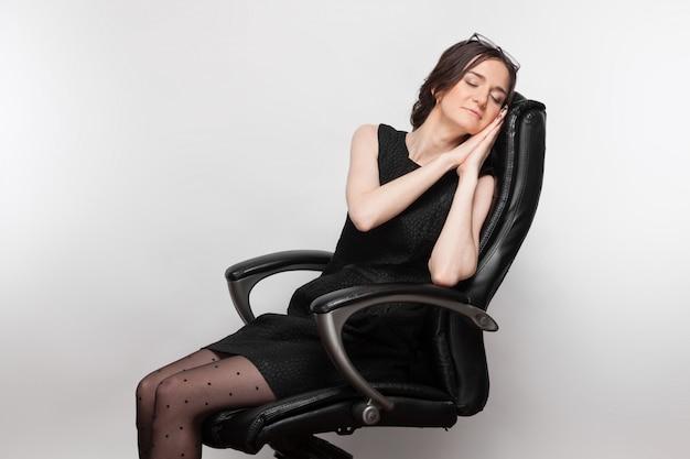 Obraz pięknej kobiety w czarnej sukni siedzi w fotelu
