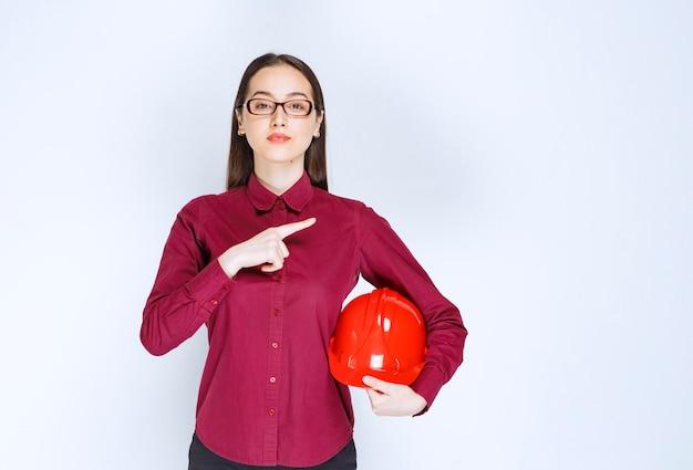 Obraz pięknej kobiety w okularach trzymając kask i wskazując palcem na bok.
