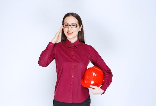 Obraz pięknej kobiety w okularach trzymając kask.