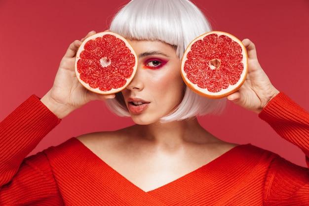 Obraz pięknej młodej kobiety na białym tle na czerwonej ścianie gospodarstwa grejpfruta.