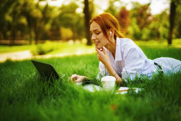 Obraz pięknej młodej ładnej rudej kobiety w parku na zewnątrz przy użyciu komputera przenośnego do nauki lub pracy