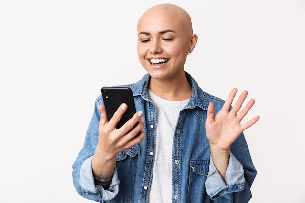 Obraz pięknej szczęśliwej łysej kobiety pozuje na białym tle, rozmawiając przez machanie telefonu komórkowego.