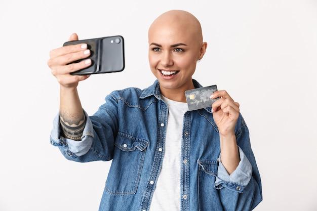 Obraz pięknej szczęśliwej łysej kobiety pozuje na białym tle, rozmawiając przez telefon komórkowy, weź selfie trzymając kartę kredytową.