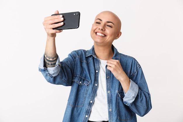 Obraz pięknej szczęśliwej łysej kobiety pozuje na białym tle, rozmawiając przez telefon komórkowy, weź selfie.