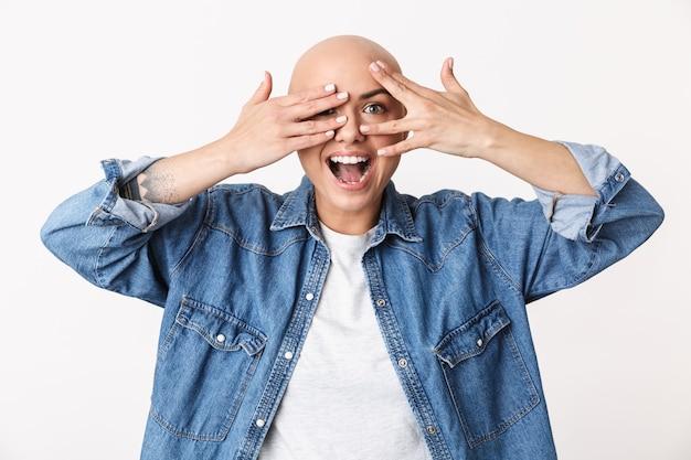 Obraz pięknej szczęśliwej łysej kobiety pozuje na białym tle, zakrywając twarz rękami.