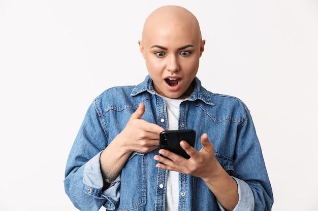 Obraz pięknej zszokowany łysa kobieta pozuje na białym tle, przy użyciu telefonu komórkowego.