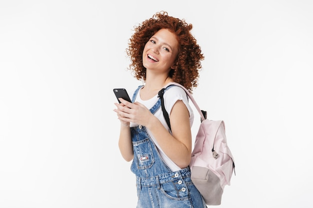 Obraz piękny kręcone szczęśliwy rude dziewczyny pozowanie na białym tle nad białą ścianą przy użyciu telefonu komórkowego.