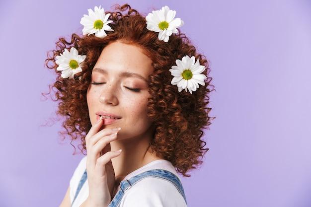 Obraz piękny kręcone szczęśliwy rude dziewczyny pozowanie na białym tle nad fioletową ścianą z kwiatami we włosach.