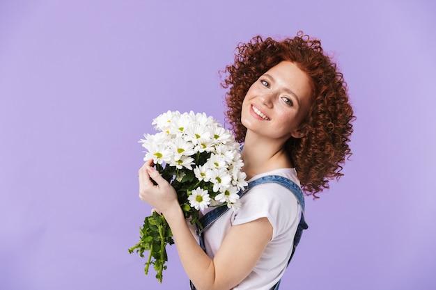 Obraz piękny kręcone szczęśliwy rude dziewczyny pozowanie na białym tle nad fioletowymi ścianami gospodarstwa kwiaty.