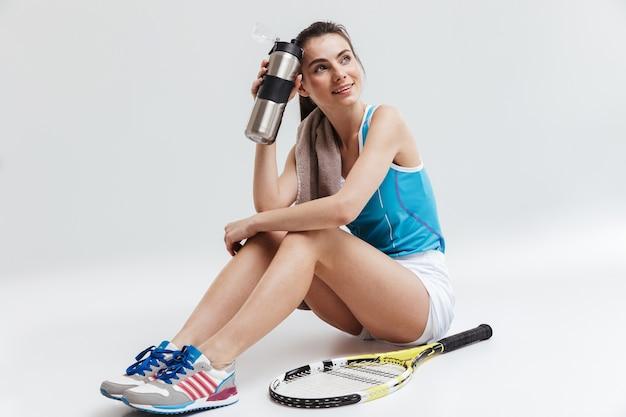 Obraz piękny młody sport fitness kobieta tenisista na białym tle nad szarą ścianą gospodarstwa wody.