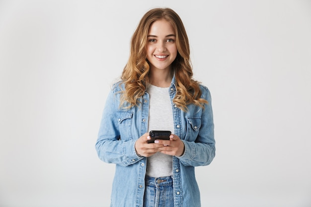 Obraz piękny młody szczęśliwy ładna kobieta pozowanie na białym tle nad białą ścianą przy użyciu telefonu komórkowego.
