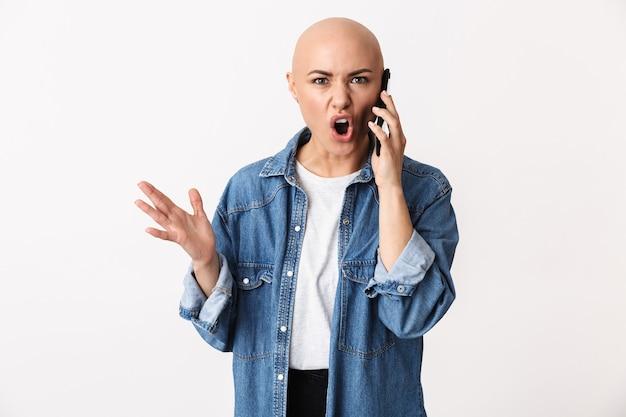Obraz piękny niezadowolony zły łysa kobieta pozuje na białym tle, rozmawia przez telefon komórkowy.