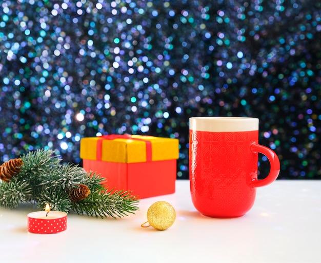 Obraz piękny świąteczny stół, świecące białe tło z czerwoną filiżanką kawy, gałąź świerku.